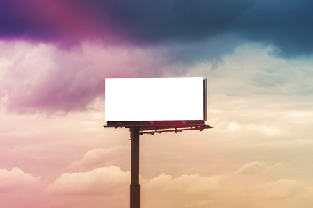 advertise: Blank Outdoor Advertising Billboard Hoarding Against Cloudy Sky, White Copy Space for Mock Up Design or Marketing Message Stock Photo