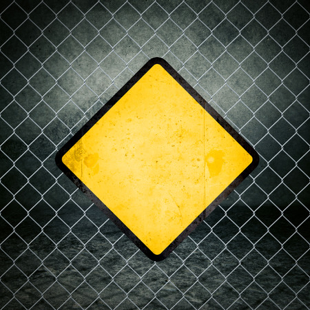 safety sign: Blank Grunge Yellow Warning Sign on Chainlink Fence of Industrial Warehouse as Copy Space for Your Message. Stock Photo
