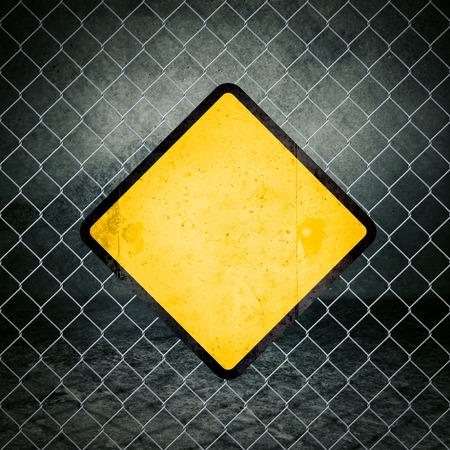 advertencia: Grunge blanco Señal de peligro amarilla en la cerca de alambre de Nave Industrial como copia espacio para su mensaje.