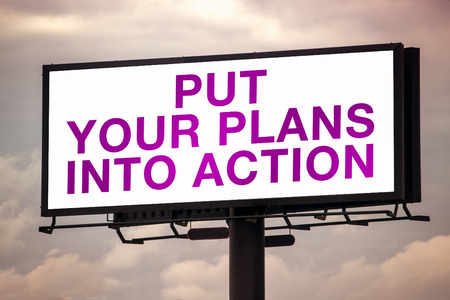 hoarding: Put Your Plans Into Action Motivational Message on Outdoor Advertsing Billboard Hoarding Against Cloudy Sky Stock Photo