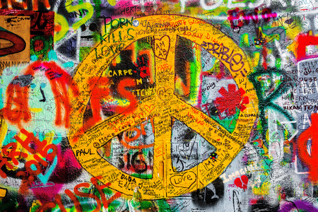 john lennon: PRAGUE, CZECH REPUBLIC - MAY 21, 2015: Peace Sign on Famous John Lennon Wall on Kampa Island in Prague filled with Beatles inspired graffiti and lyrics since the 1980s.