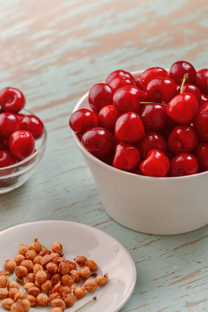 pits: Sweet Cherry in Bowl on Rustic Table, Ripe Fresh Wild Cherries Fruit and Pits