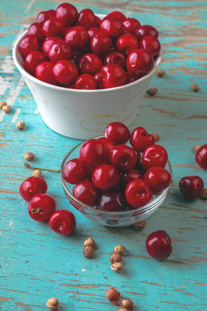 pits: Cherry Bowl on Rustic Table, Ripe Fresh Wild Cherries Fruit and Cherry Pits
