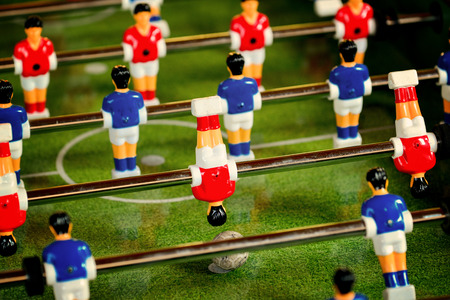 kicking ball: Vintage Foosball, Blue and Red Players Team in Table Soccer or Football Kicker Game, Selective Focus, Retro Tone Effect Stock Photo