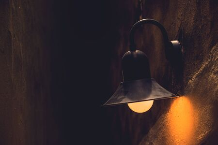 Vintage Street Light Lamp at Night, Mounted on Weathered Concrete Wall.