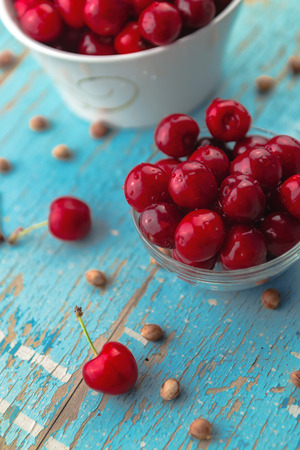 pits: Cherries in Bowl on Rustic Table, Ripe Fresh Fruit and Cherry Pits as Dieting Concept Stock Photo