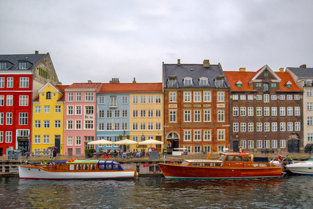 entertainment district: COPENHAGEN, DENMARK - JUNE 27, 2015: Copenhagen Nyhavn Canal and District with its Colorful Facades on Cloudy Rainy Day, Beautiful Romantic Place is a 17th Century Waterfront, Nowdays an Entertainment District in Danish Capital. Editorial