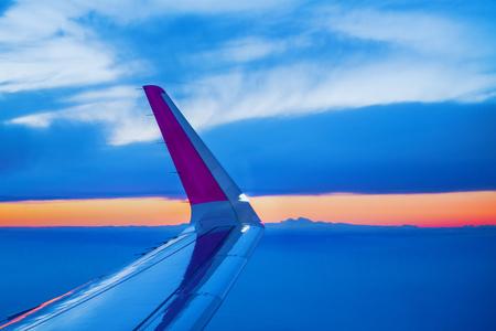 anuncio publicitario: Avión de ala vista a través de la porta Ventana Abierta Durante el vuelo de los aviones de pasajeros comerciales, la puesta del sol en horizonte