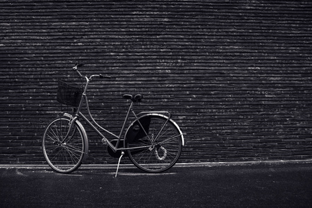 urban culture: Classic vintage hipster bicycle leaning against the street wall, urban setting, cyclcing culture and healthy lifestyle concept, black and white monochromatic  like retro toned image