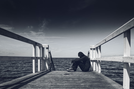 solitude: Alone Young Man Sitting at the Edge of Wooden Pier - Hopelessness, Solitude, Alienation Concept, Black and White Stock Photo