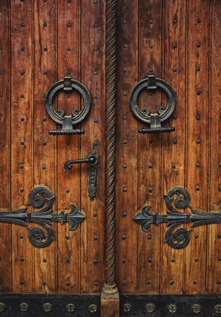 Old carved wooden church door with hinges