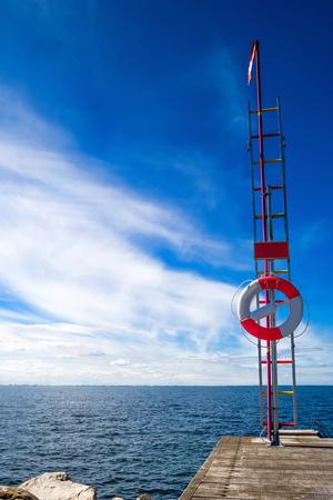 resort life: Red and White Life Buoy on Seashore of Coastal Summer Vacation Resort