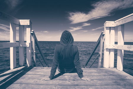 hopelessness: Alone Young Woman Sitting at the Edge of Wooden Pier Looking at Water - Hopelessness, Solitude, Alienation Concept, Black and White