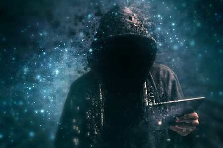 Pixelated unrecognizable faceless hooded cyber criminal man using digital tablet in cyberspace