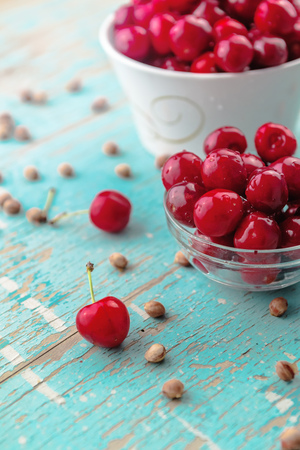 fruit drop: Sweet Cherry in Bowl on Rustic Table, Ripe Fresh Wild Cherries Fruit and Cherry Pits Stock Photo