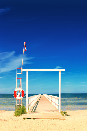 layoff: Wooden Ocean Pier with Lifebuoy in Coastal Summer Vacation Resort Stock Photo
