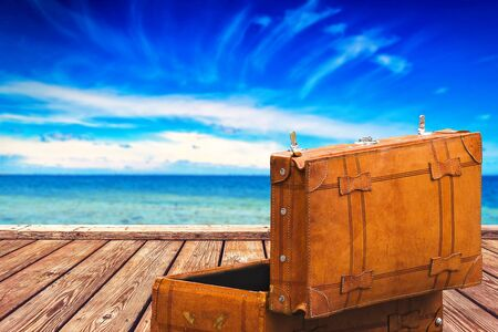 horizon over water: Open Vintage Suitcase at Wooden Boardwalk Pier and Open Wide Sea with Horizon over Water, Background for Object Placement