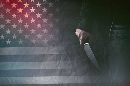 male killer: American serial killer, male hand with sharp knife and grunge USA flag in background, retro toned image