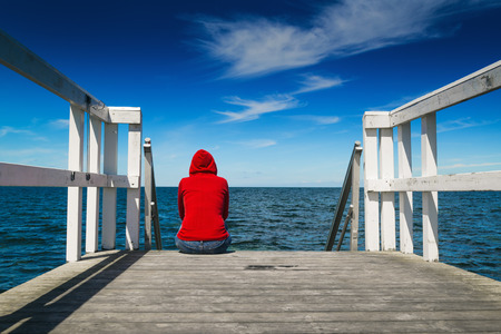 Alone Young Woman in Red Hooded Shirt Sitting at the Edge of Wooden Pier Looking at Water - Hopelessness, Solitude, Alienation Concept Foto de archivo