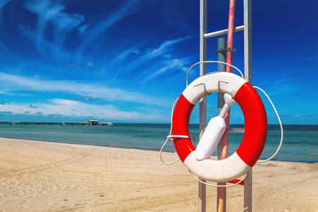 resort life: Lifebuoy, Red and White Life Preserver on Sandy Beach of Coastal Summer Vacation Resort Stock Photo