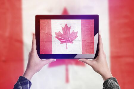 citizenry: Person Taking Picture of Canada Flag with Digital Tablet Computer, Vintage Tone Retro Effect Stock Photo