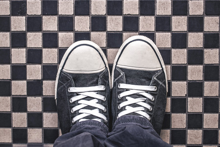 casual men: Gray Sneakers on Checkered Pattern Pavement, Top View, Overhead Shot of Man Standing on Street, Urban Lifestyle Concept
