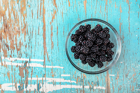 eating healthy: Blackberries in glass bowl on rustic wooden table, fresh fruit for healthy eating benefits, blank copy space, top view