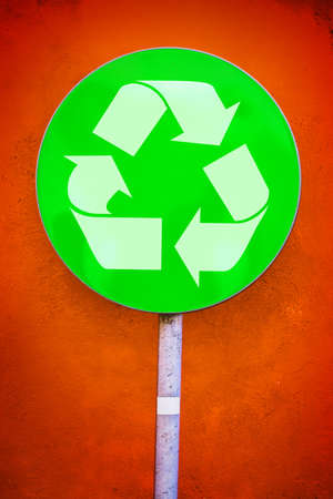 environmentalist: Recycle Symbol on Green Ecology Round Traffic Sign Against Orange Grunge Wall, Urban Environmentalist Concept Stock Photo
