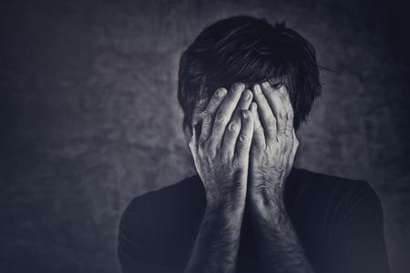 un homme triste: Chagrin, homme couvrant la FSCE et les pleurs, image monochromatique