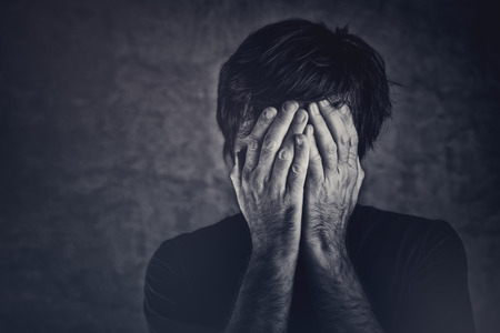 Grief, man covering fsce and crying, monochromatic image Stock Photo