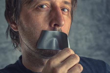 Fighting censorship, adult caucasian man removing duct tape from mouth that prevented him from speaking, freedom of speech and expression concept