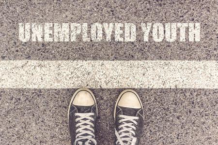 file d attente: Les jeunes chômeurs d'attente en ligne, vue de dessus, l'homme debout à la ligne frontière sur une chaussée urbaine, les jeunes pieds mâles portant des baskets derrière la ligne