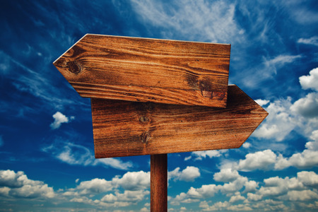 Blank Rustic Opposite Direction Wooden Sign Against Blue Sky with Clouds, Concept of Choice, Choosing Your Life Path.