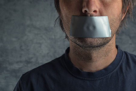 Censorship, adult caucasian man with duct tape on mouth to prevent him from speaking, freedom of speech and expression concept