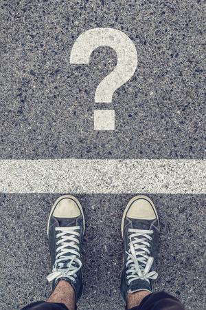 juventud: Joven de pie en el cuestionamiento de la calle, zapatillas de deporte desde arriba en la carretera de asfalto con signo de interrogación, el estilo de vida de la juventud urbana, vista superior