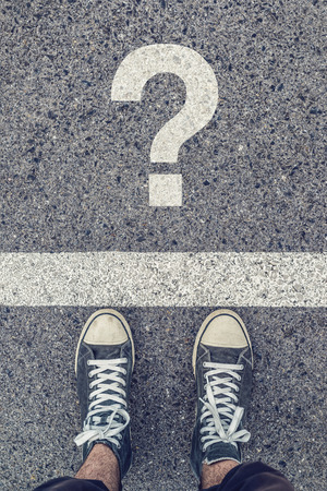 urban youth: Young man standing on the street questioning, sneakers from above on asphalt road with question mark, urban youth lifestyle, top view