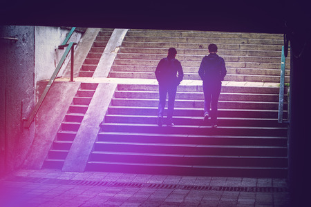 underground passage: People in Urban Environment, Pedestrians Walking in Underground Passage, Silhouettes of Two Women Climbing Concrete Stairs, Vintage Retro Tone Effect Stock Photo