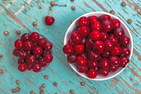 pits: Sweet Cherry in Bowl on Rustic Table, Ripe Fresh Wild Cherries Fruit and Cherry Pits, top view