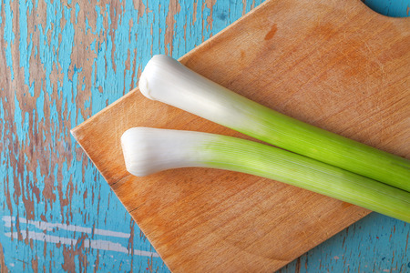 leek: Leek on cutting board on rustic wooden kitchen table, fresh green vegetable for healthy eating benefits, top view
