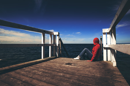 hooded shirt: Alone Young Woman in Red Hooded Shirt Sitting at the Edge of Wooden Pier Looking at Water - Hopelessness, Solitude, Alienation Concept, Retro Toned