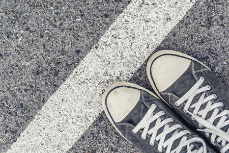 pies masculinos: Hombre joven colas siguiente en la línea, hombre de pie en la línea de frontera en el pavimento urbano, vista desde arriba de pies masculinos llevaban zapatillas de deporte Foto de archivo