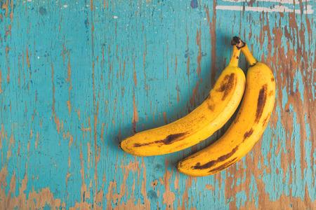 banana: Hai quả chuối chín già trên bàn gỗ mộc mạc, nhìn từ trên xuống