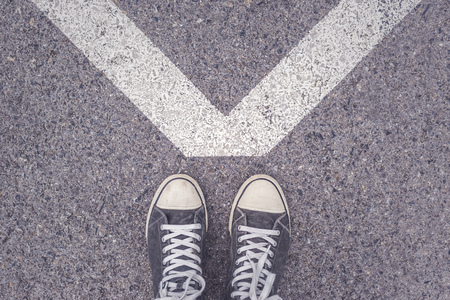 pavement: Man standing above V shaped sign on urban pavement, top view of young male feet wearing modern kicks or sneakers, concept of victory