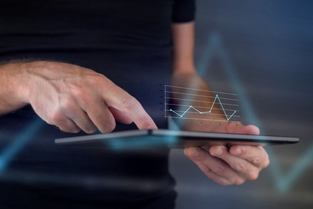 Business chart diagram on digital tablet computer, hans tapping touch screen to view financial report. Banque d'images