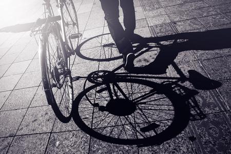 pavement: Man Pushing Bicycle, Street Shadow on Pavement, Urban Setting, Retro Toned Monochromatic Image Stock Photo