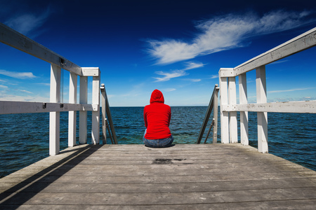 solitude: Alone Young Woman in Red Hooded Shirt Sitting at the Edge of Wooden Ocean Jetty Looking at Water - Hopelessness, Solitude, Alienation Concept