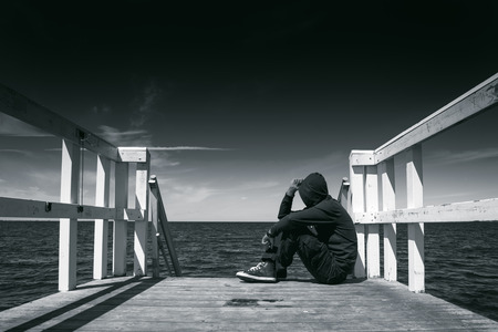 alienation: Alone Man Sitting at the Edge of Wooden Pier, Looking at Water - Hopelessness, Solitude, Alienation Concept, Black and White Stock Photo