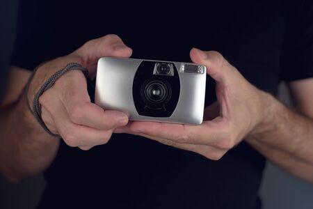 AFICIONADOS: El hombre la toma de fotografías instantáneas con la cámara de película de plástico genérico vintage, aficionado lomo photography concepto de estilo de vida inconformista, enfoque selectivo Foto de archivo