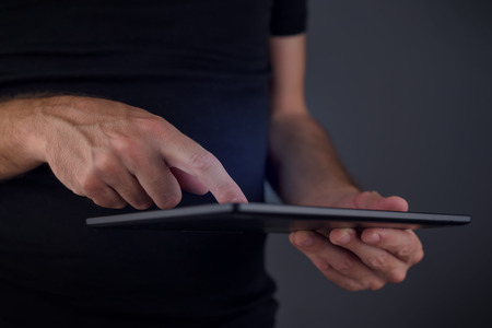 Digital tablet computer usage, man tapping touch screen of moveable electronics technology gadget, close up of hands, selective focus on finger