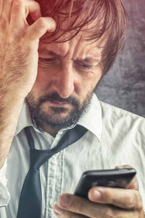 bad news: Portrait of worried businessman received bad news via SMS message or e-mail on mobile smart phone, selective focus on face